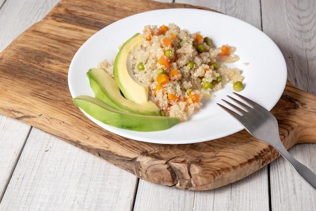 木の板の白い平板に野菜とアボカドが入ったキノアのお粥。