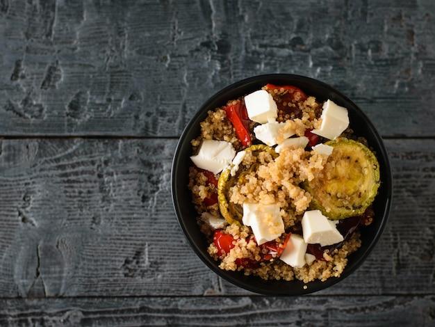 Салат из киноа и запеченные овощи в черной миске на белом столе