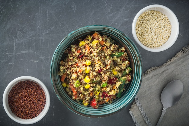 Quinoa salad bowl with vegetables: carrot, corn, bell pepper, peas and two bowls with red and white quinoa