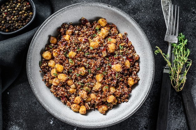 Quinoa salad with chickpeas and thyme. super food. black background. top view.