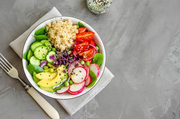Салат из киноа со свежими овощами, шпинатом, зеленым горошком, микрозеленью и семенами кунжута в миске на бетонном фоне. концепция здорового питания. горизонтальная ориентация. вид сверху, копия пространства.