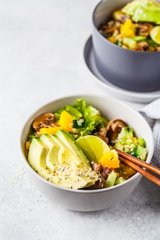 Quinoa salad with mushrooms, vegetables and avocados in gray bowl. healthy vegan food concept.