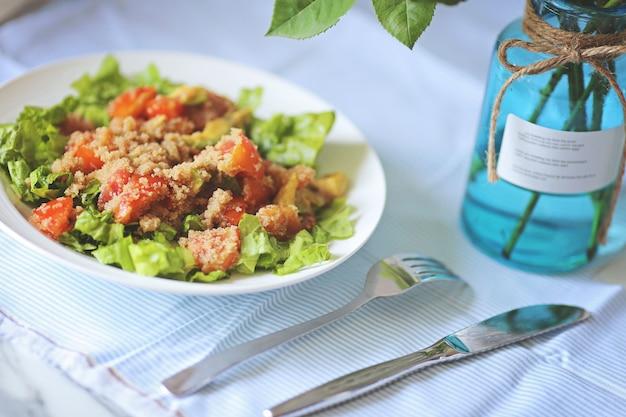 生地の自然な色の背景にサラダの葉、アボカド、トマトのキノアサラダ。スーパーフードのコンセプト。選択的な焦点。テーブルで提供
