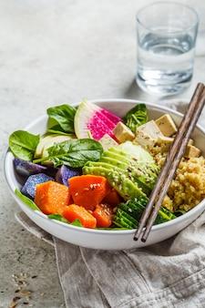 Салат из киноа с тофу, авокадо и овощами в белой миске