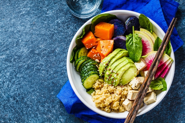 Quinoa salad with tofu, avocado and vegetables in white bowl