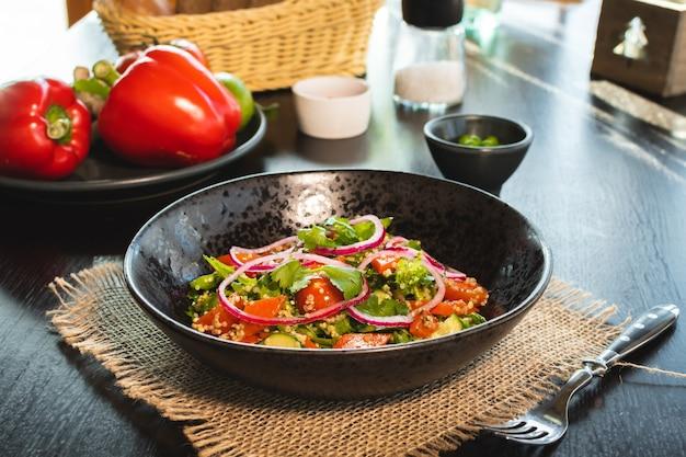 Салат из киноа с помидорами, авокадо, паприкой и петрушкой на черной каменной тарелке.