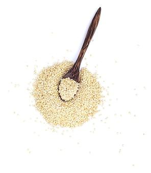 Семена киноа в деревянной ложке, изолированные на белом пространстве. вид сверху