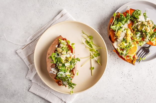 Quinoa stuffed sweet potatoes with kale and avocado, top view.