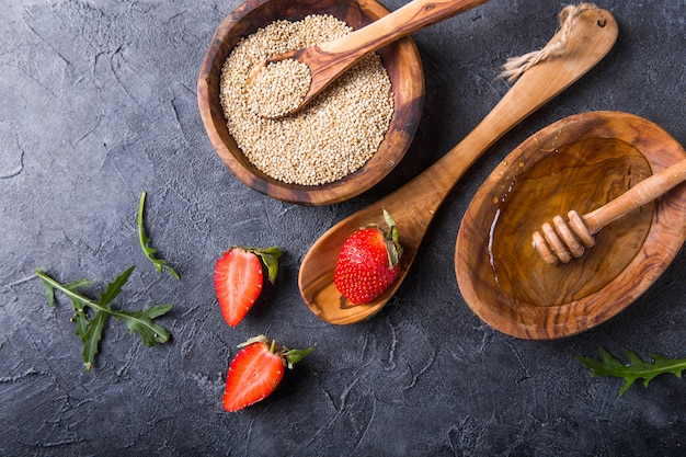 Quinoa white grains in a wooden bowl and spoon with strawberry, honey. gluten free healthy food
