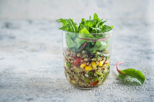 Quinoa with vegetables in a glass cup with lettuce leaves
