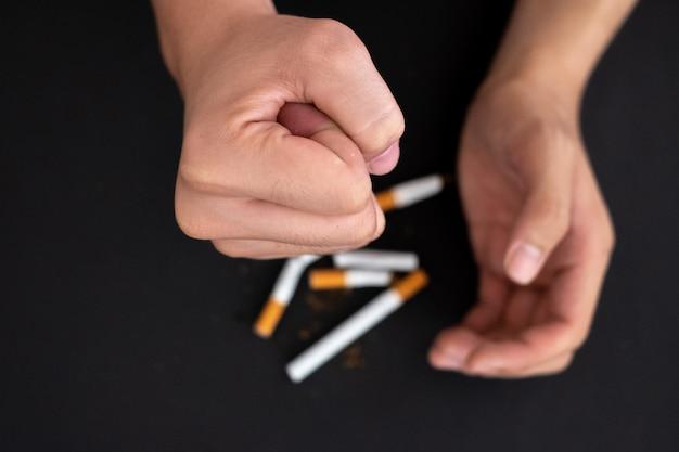 Бросить курить, рука держать сигарету уничтожить, изолированных на черном