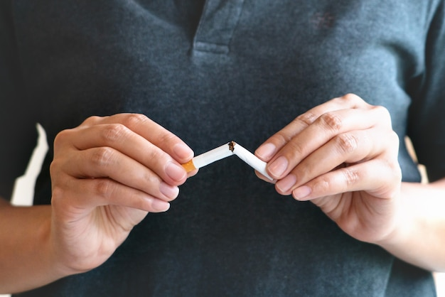 Quit smoking, no tobacco day, woman hands breaking the cigarette