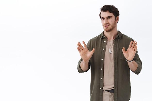 Бросьте эту чушь. серьезно выглядящий занятой красивый парень показывает стоп, достаточно или не жестикулирует с поднятыми руками возле груди
