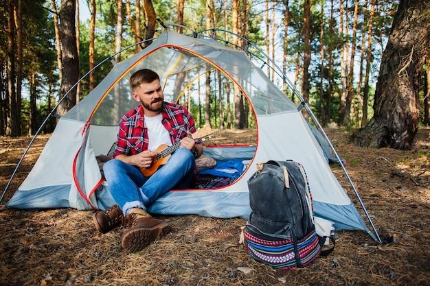 Quitarを演奏するテントの中で若い男