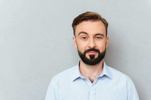 Quizzical bearded man in business clothes looking at the camera