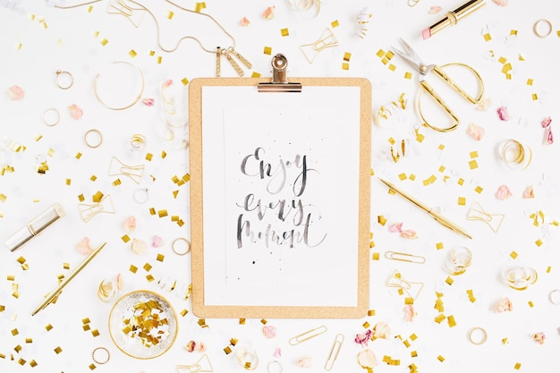 Quote enjoy every moment clipboard and gold style feminine accessories pattern golden tinsel scissors pen rings necklace bracelet on white background flat lay top view