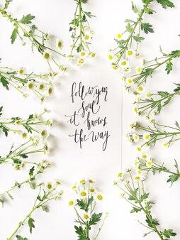 Цитата «следуй своей душой, она знает путь», написанная каллиграфически с цветами.