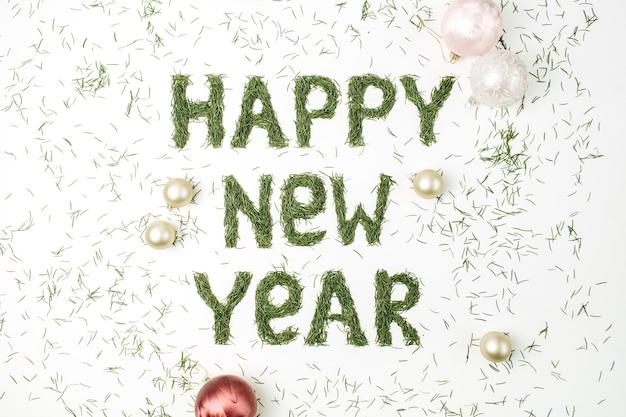 白い表面に針葉樹の針とクリスマスボールの装飾で作られたhappynewyearを引用してください。フラットレイ、上面図