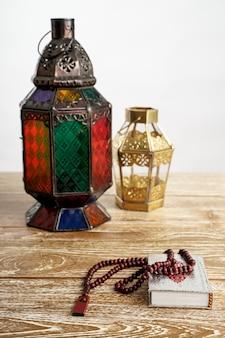 Quran arab lantern and pray beads on white