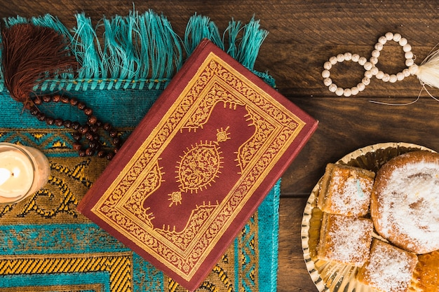 Quran and beads near candle and pastry
