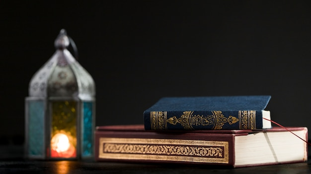Quran book on table with candle beside