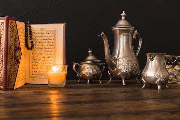 Quran and candle near tea set