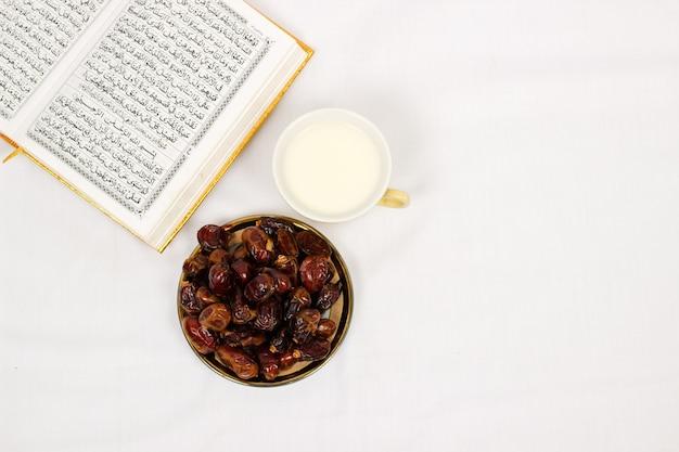コーランの日付と白い背景で隔離のミルクのガラス