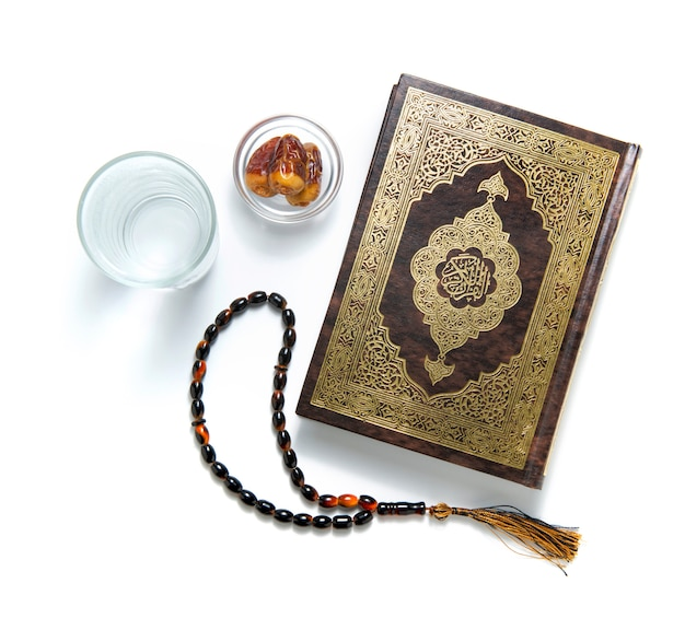 Quran holy book, water, dates and rosary, isolated on white