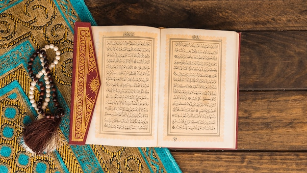 Quran near beads and patterned rag