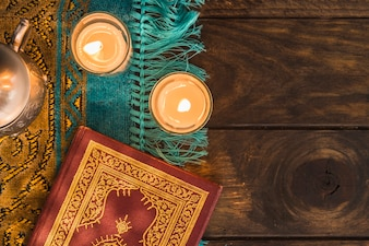 Quran near burning candles and pot