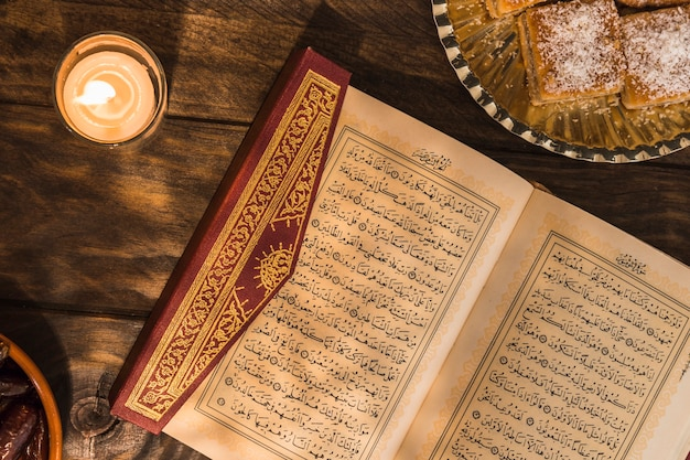 Quran near candle and dessert