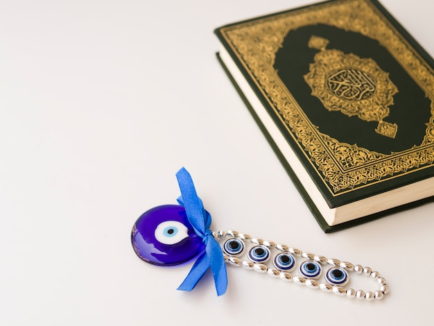 Quran on table with eye of allah amulet