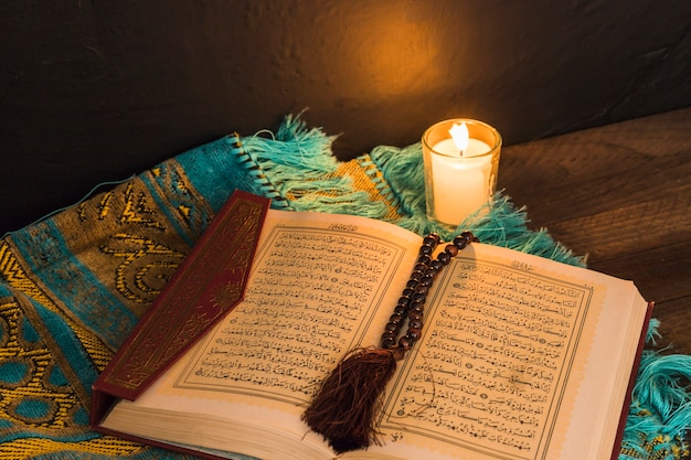 Quran with beads and candle on mat