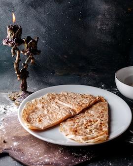 Pasto di pasta qutab con carne e zucca all'interno del piatto bianco sulla superficie grigia