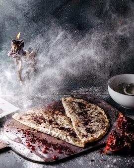 Delizioso piatto di carne e zucca di qutab versato con farina con fette di melograno e sumax sulla superficie grigia