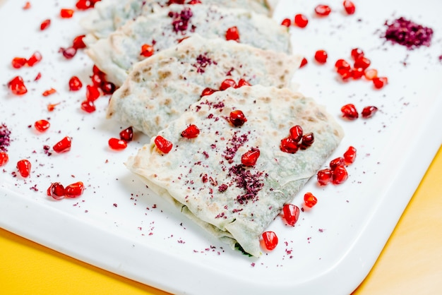 Qutabs topped with sumakh and pomegranate
