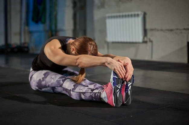 R girl in gray leggings doing stretching. sports gym in industrial style.
