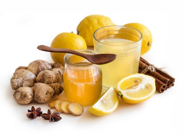 白で隔離される蜂蜜、レモン、ジンジャートニックrをクローズアップ