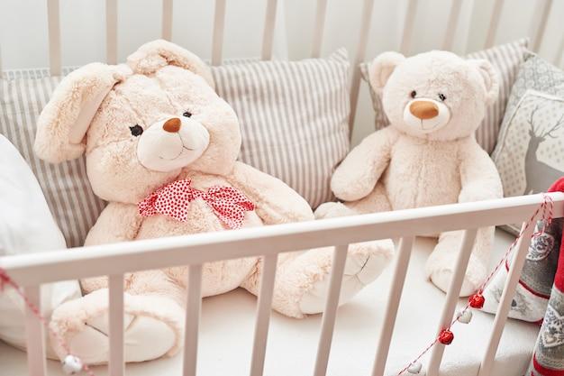 흰 침대에서 토끼와 곰. 어린이 침실의 부드러운 장난감. 화이트 키즈 룸.