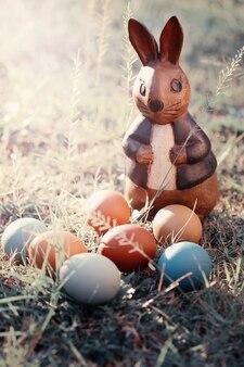 カントリースタイルのウサギとカラフルなイースターエッグ。イースターコンセプトの背景。