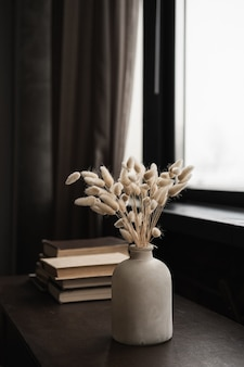 Rabbit bunny tail grass bouquet, books stack on solid wooden table against window.