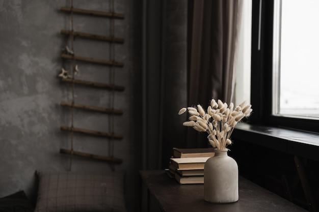 鍋にウサギのウサギの尾草の花束、本は窓に対してテーブルに積み重ねられます