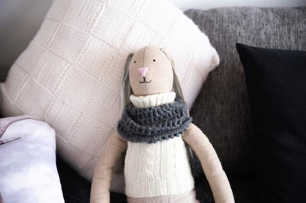 Кукла-игрушка кролик лежит на кровати с подушками