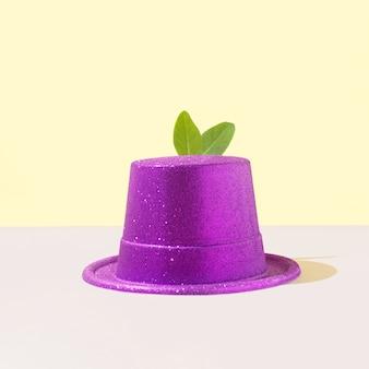 光沢のある紫色の帽子をかぶった緑の葉で作られたウサギの耳。クリエイティブな東部のミニマルシーン。