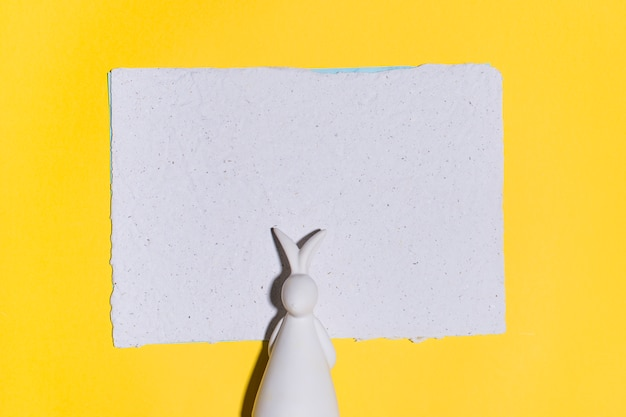 Rabbit figurine with paper on yellow table