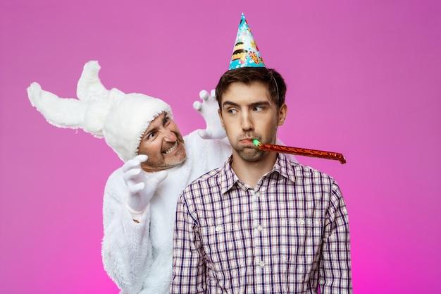 Rabbit frightening drunk man over purple wall. birthday party.