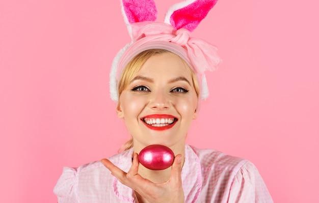 토끼소녀. 부활절 날. 토끼 귀를 가진 행복한 여자는 분홍색 부활절 달걀을 보유하고 있습니다. 계란 사냥. 봄 방학.