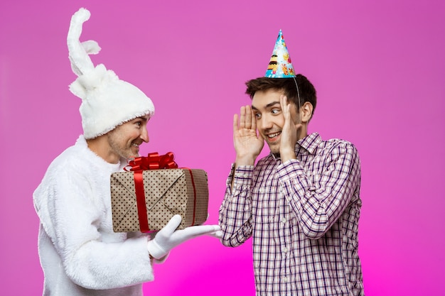 Rabbit giving birthday gift to drunk man over purple wall.