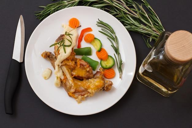 칼과 로즈마리가 있는 세라믹 접시에 베샤멜 소스와 함께 화이트 와인에 구운 토끼 다리. 오븐에서 요리한 식이 토끼 고기. 평면도.