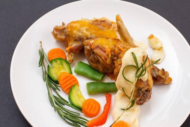 Ножки кролика, запеченные в белом вине с соусом бешамель на керамической тарелке с овощами и розмарином. диетическое мясо кролика, приготовленное в духовке. вид сверху.